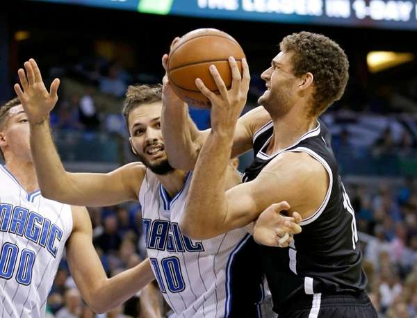 Orlando Magic's Evan Fournier (10) fouls Brooklyn Nets'