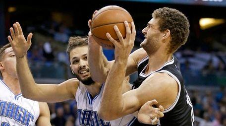 Orlando Magic's Evan Fournier (10) fouls Brooklyn Nets'