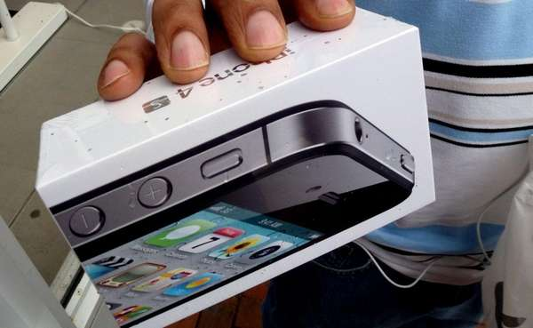 A man holds his new iPhone 4S outside