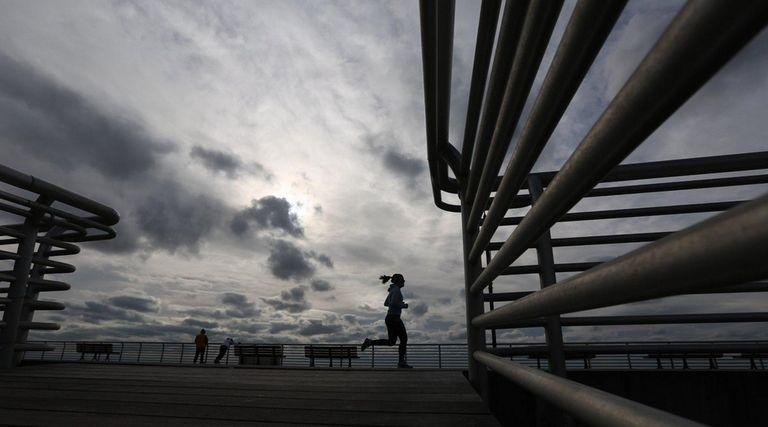 A woman runs along the boardwalk in