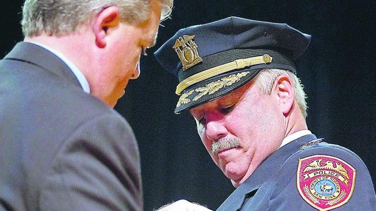 Suffolk County Executive Steve Bellone pins a police