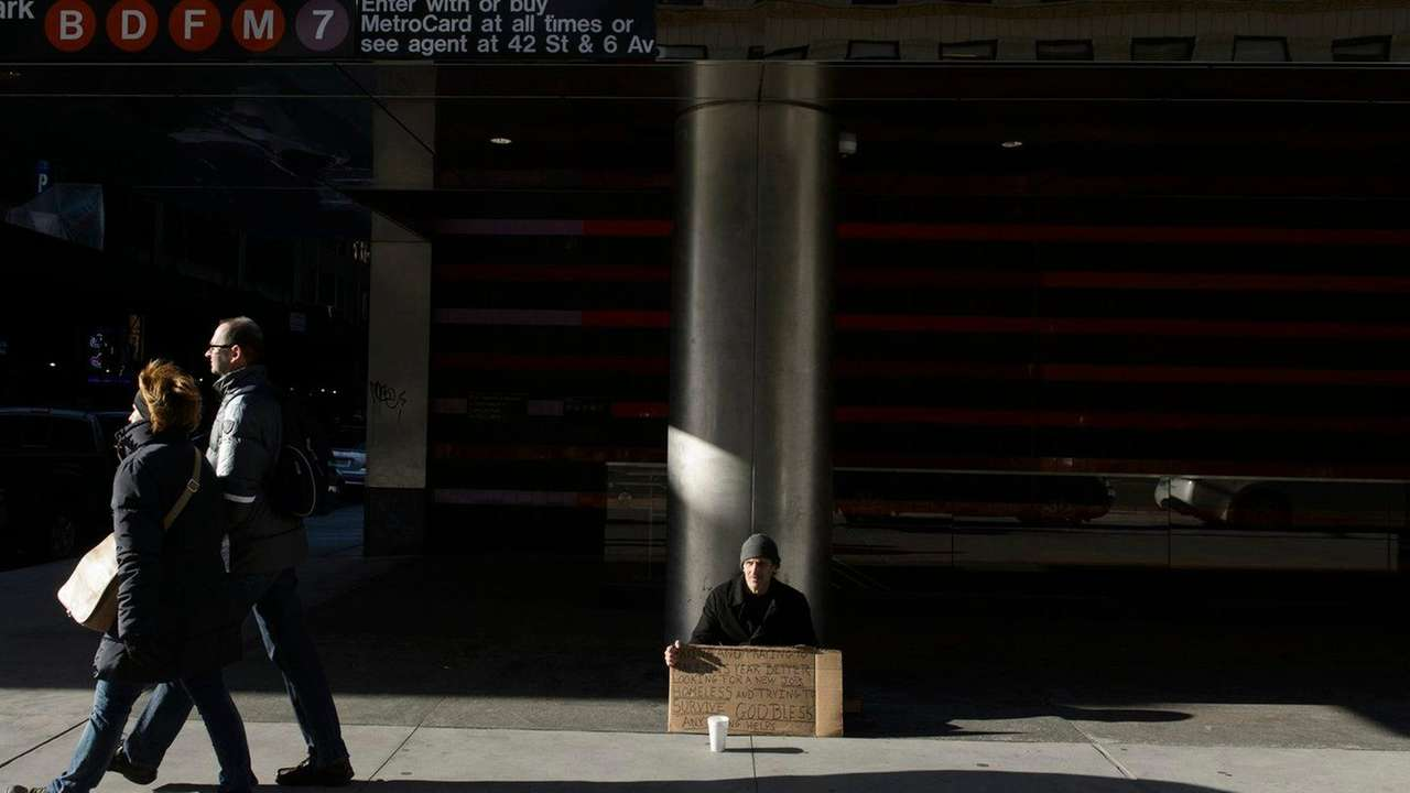 A homeless man sits on Sixth Avenue and