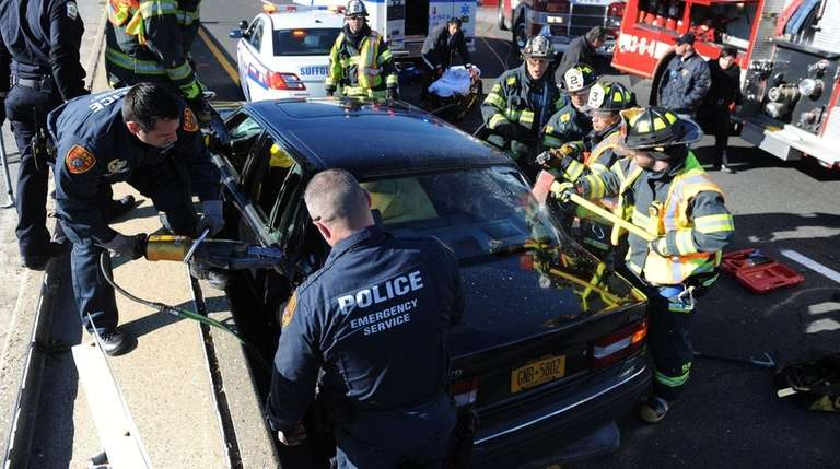 Emergency personnel work to cut free a