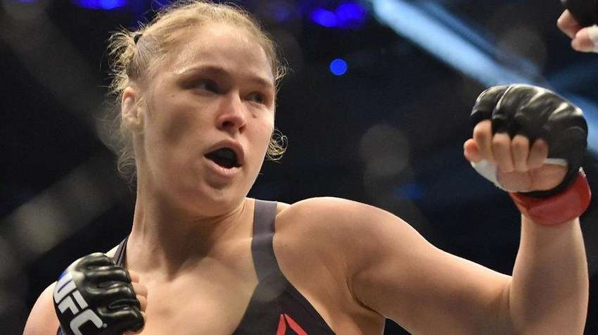 Ronda Rousey, left, lines up Holly Holm during