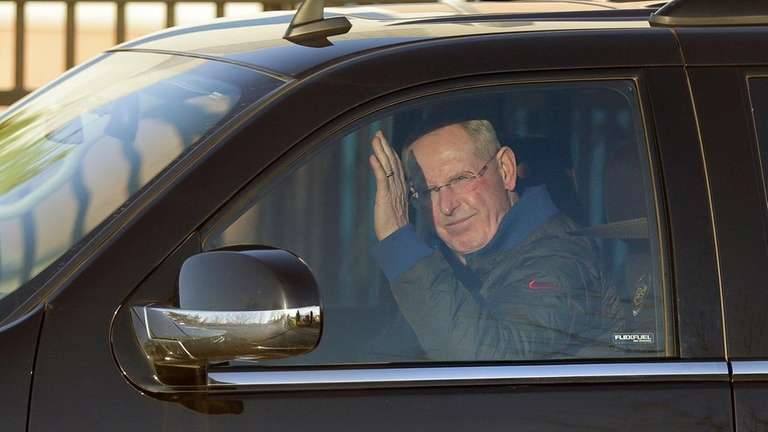 Tom Coughlin waves to photographers as he leaves