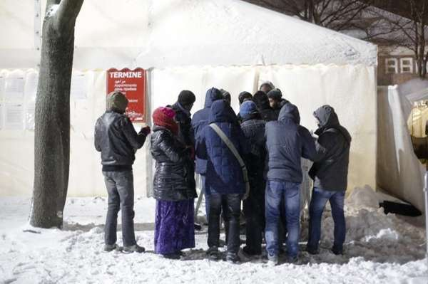 Migrants line up for an appointment in front