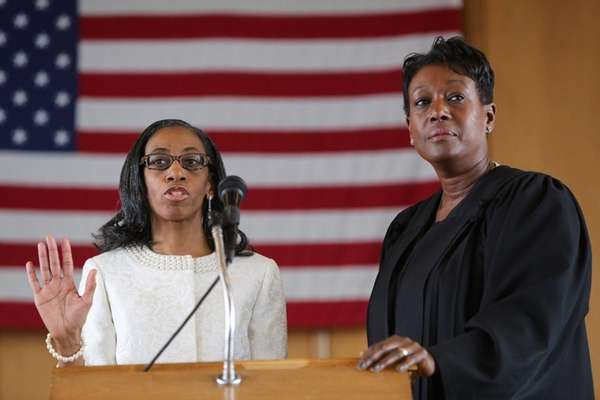 Anissa Moore, left, is sworn in as a