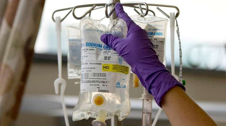 A nurse places a patient's chemotherapy medication on