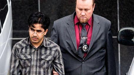 Omar Faraj Saeed Al Hardan, left, is escorted