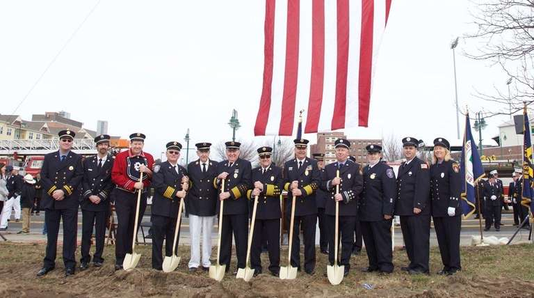 Local firefighters hold golden shovels during a groundbreaking