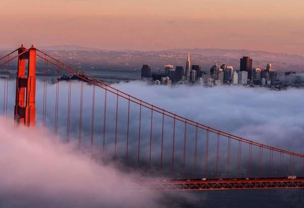 The Golden Gate Bridge, shrouded in clouds, with