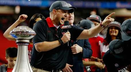 Houston coach Tom Herman celebrates alongside the trophy