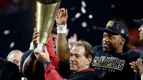 Alabama head coach Nick Saban celebrates by hoisting