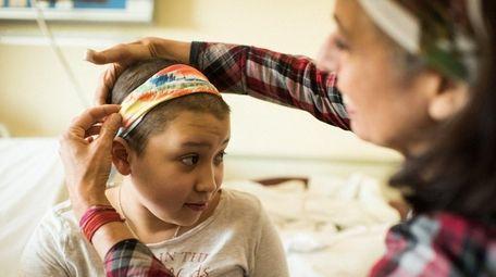 Joanie Accolla helps Esmeralda, 11, with a headband