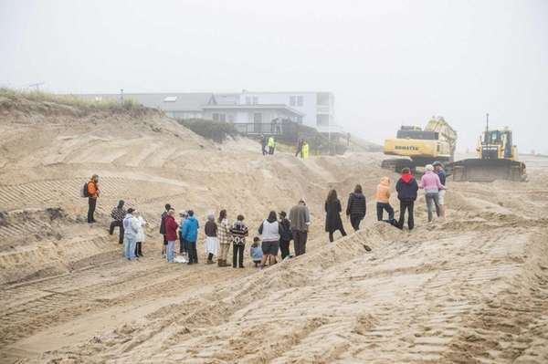 Protesters stand in a pit at an excavation