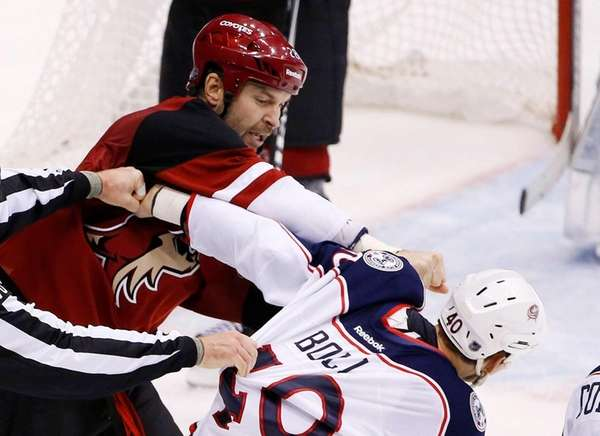 Arizona Coyotes' John Scott, left, punches Columbus Blue