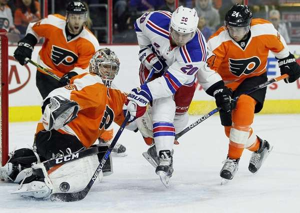 Philadelphia Flyers' goalie Steve Mason, left, defends against