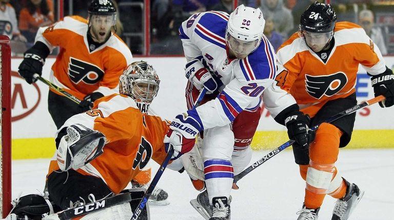 Philadelphia Flyers' goalie Steve Mason, left, defends against