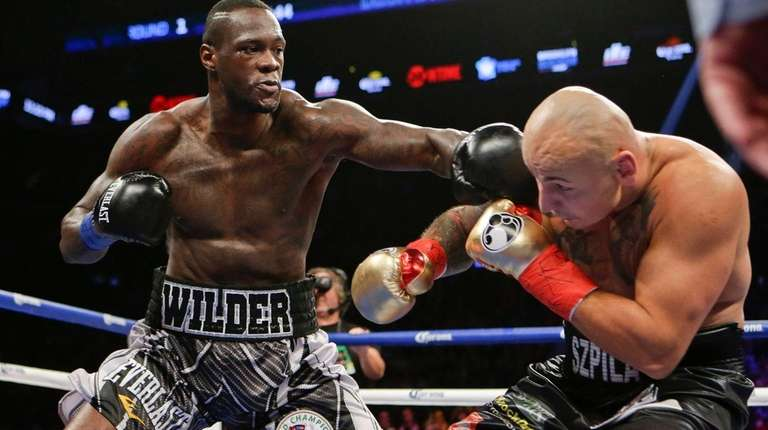 Deontay Wilder punches Artur Szpilka, of Poland, during