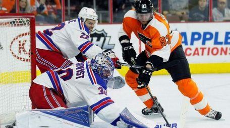 New York Rangers goalie Henrik Lundqvist deflects the