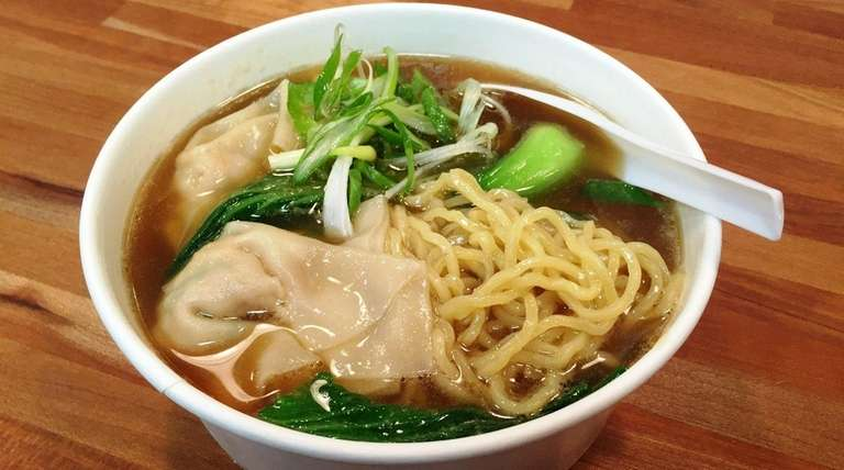 Ramen noodles with chicken wontons are on the