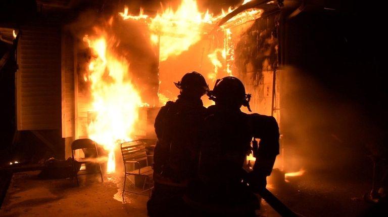 Firefighters battle a house fire on Verrazano Avenue