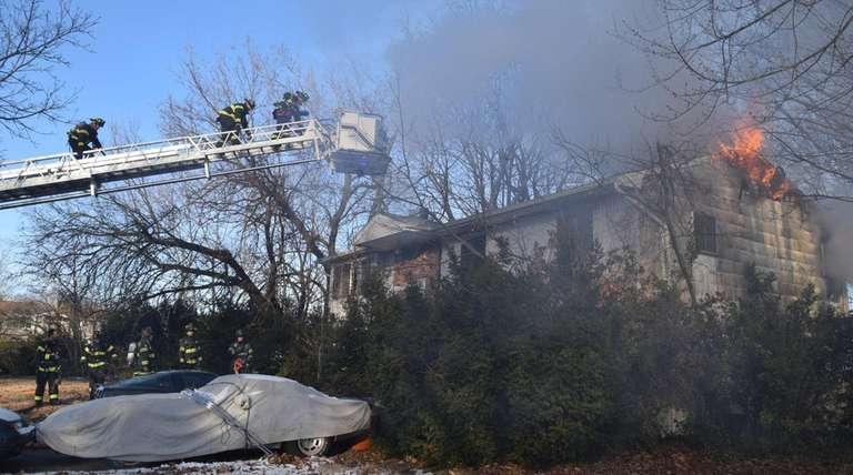 Firefighters work the scene of a house