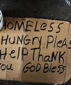 A homeless man's sign rests on the