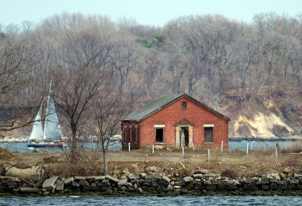 A sailboat passes behind an abandoned building on