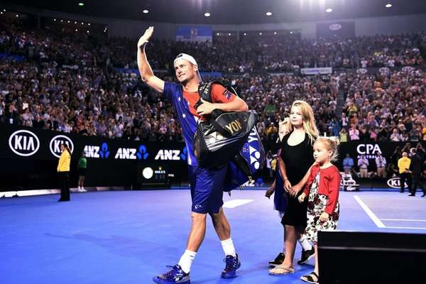 Lleyton Hewitt, left, leaves the court with