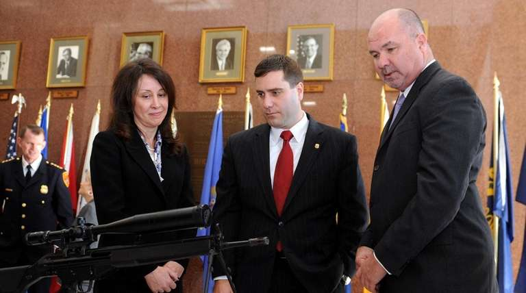 Suffolk County Police Commissioner Tim Sini, center, joins