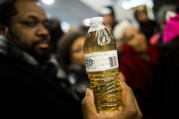 Pastor David Bullock holds up a bottle of