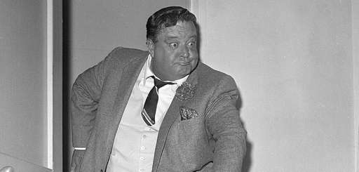 Comedian Jackie Gleason clowns for photographers after