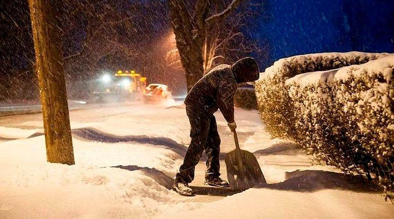 Angelo Nomina shovels the sidewalk in front of