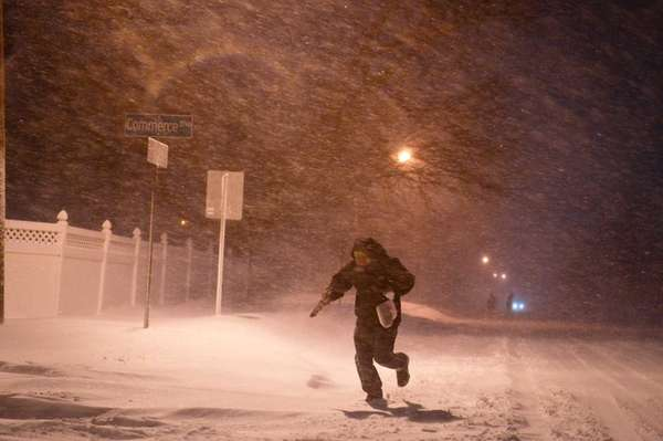 A man runs through the snow along Commerce
