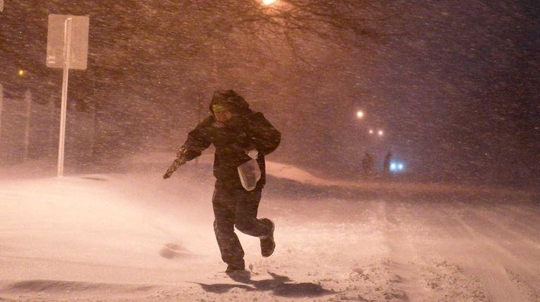 A man runs through the snow along Commerce