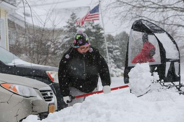 Christina Campbell uses a shovel to clear snow