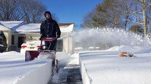 Matt Bokee, 33, of Calverton, blows the snow