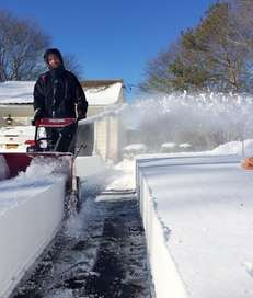 Matt Bokee, 33, of Calverton, blows the snow