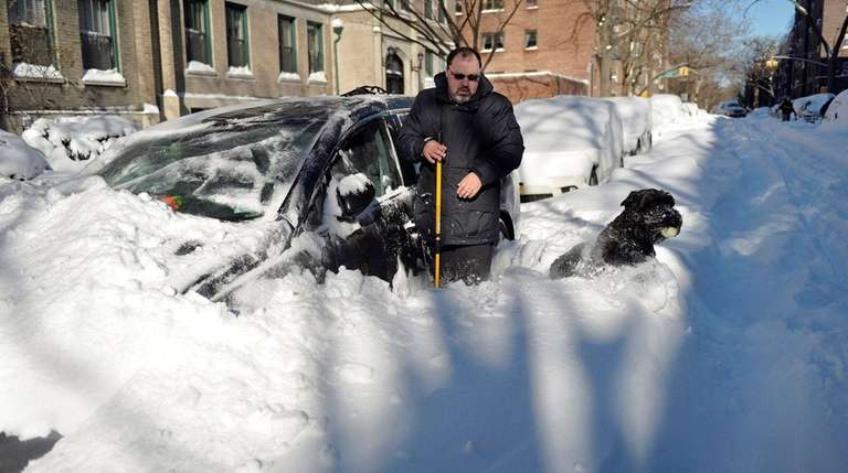 Anatoly Hazan begins to dig out his car