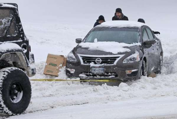 Passers-by help push a stuck car out of