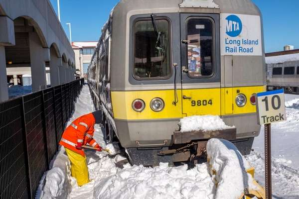 A Long Island Rail Road worker shovels snow