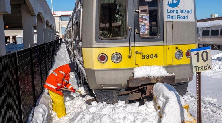 A Long Island Rail Road worker shovels snow