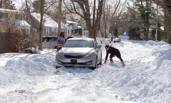 A woman digs a car out on South