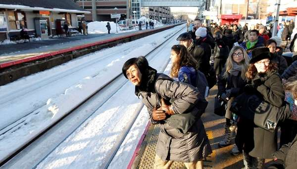 Morning commuters crowd platform as they wait