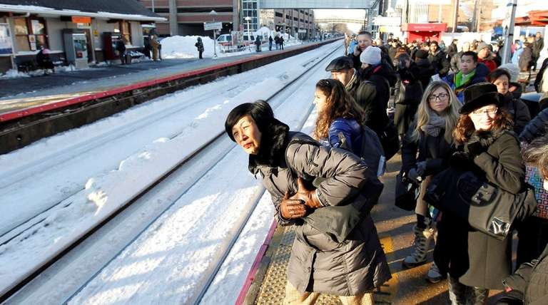 Morning commuters crowd the platform as they wait