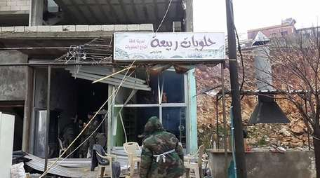 Pro-government forces inspect a building in Rabia in
