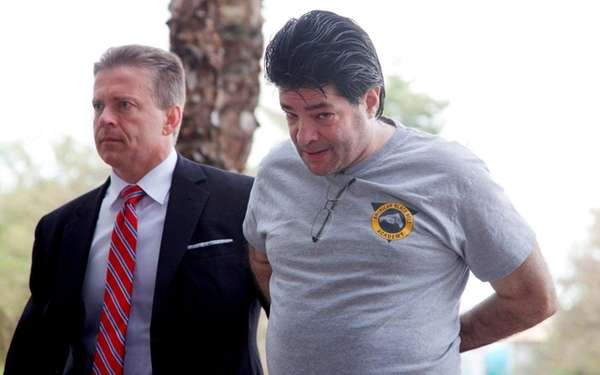 Aaron Wider, right, is escorted by a