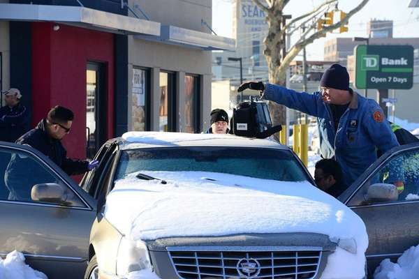 Emergency personnel surrounding a Cadillac Monday, Jan. 25,