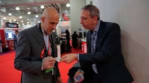 Seth Kramer, right, a corporate magician from Huntington,